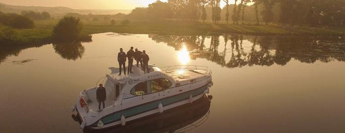 Mehrere Personen bei Sonnenuntergang auf einem Hausboot