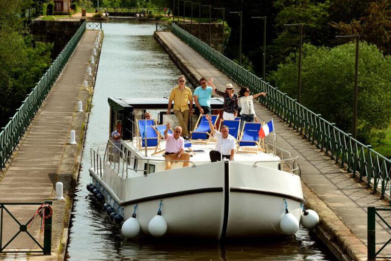 Eine Familie sitzt an Deck eines Hausbootes auf einem Fluss