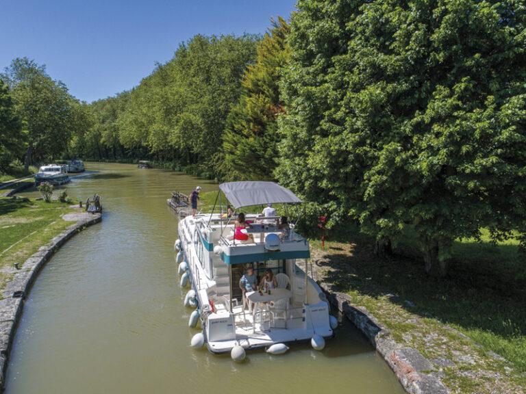 Ein luxeriöses Hausboot mit mehreren Etagen auf einem Fluss